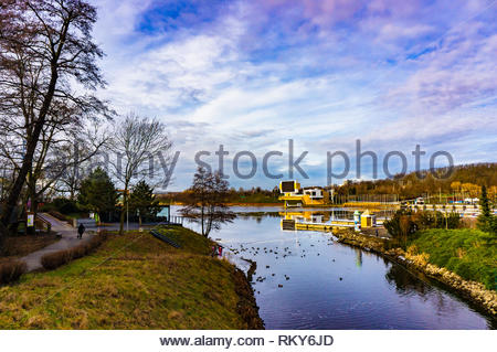 Poznan, Poland - February 10, 2019: Lake with many ducks at the Malta park on a cloudy day. This location is very popular for water sport. - Stock Image