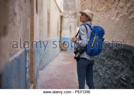 Young female tourist explores the houses in Essaouira, Morocco. - Stock Image