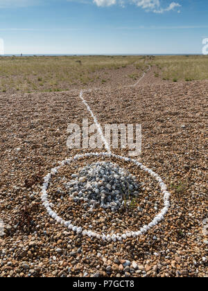 Small stone and shell cairn on a shingle beach in a ring of white sea shells and a line running from it down to the sea, Shingle Street,Suffolk - Stock Image