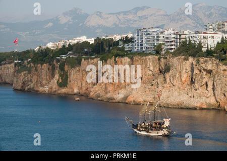 Wooden tourist boat on sightseeing trip along dramatic coastline in Antalya, Turkey - Stock Image