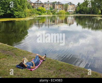 A woman reading by a lake on Hampstead Heath in London UK - Stock Image