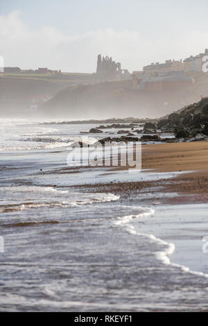 Whitby, Yorkshire, UK. 11th February, 2019. U.K. Weather. Whitby, North Yorkshire, England. 11th February 2019. Whitby Abbey on a cold, bright and misty morning with the tide going out along the North Yorkshire Coast. Alan Beastall/ /Alamy Live News - Stock Image
