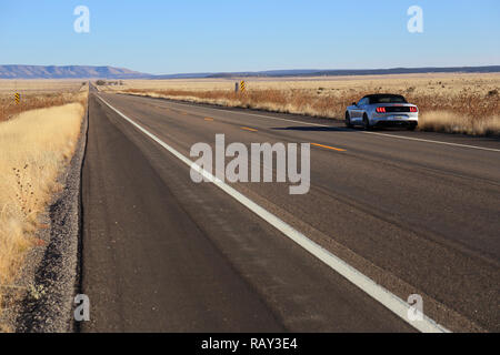 Long, straight stretch of road on Route 66 and an american Ford Mustang in the roadside - Stock Image