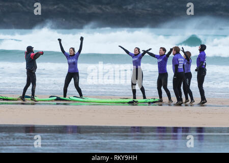 Novice surfers warming up with their instructor at the start of a surfing lesson at Fistral Beach in Newquay in Cornwall. - Stock Image