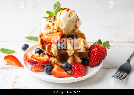 Stack of waffles with blackberries and strawberrys, vanilla ice cream and caramel syrup on a white wooden table - Stock Image