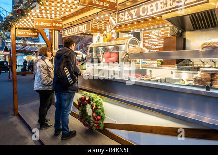 Customers at a street foot stall selling hot, cheese-based fare, including Halloumi Fries and Cheese Toasties and Beef Brisket. George Square, Glasgow - Stock Image