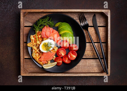 potato waffles with salmon, egg, avocado and tomatoes on a black plate on a dark background. view from above. - Stock Image