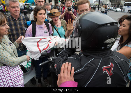 London, UK. 24th April 2019. A motorcyclist contests climate change activists from Extinction Rebellion blocking roads around Parliament Square on the - Stock Image