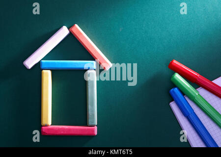 Close-up of chalk house and highlighters on blackboard - Stock Image