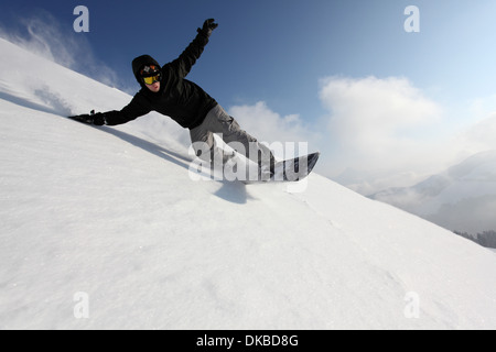 Snowboarder going down mountain - Stock Image