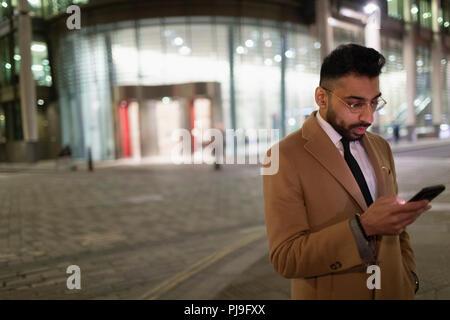 Businessman texting with smart phone on urban street corner at night - Stock Image