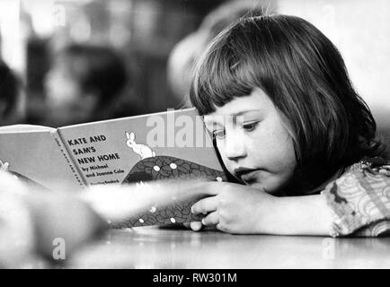 A young girl engrossed in a book at school - Stock Image