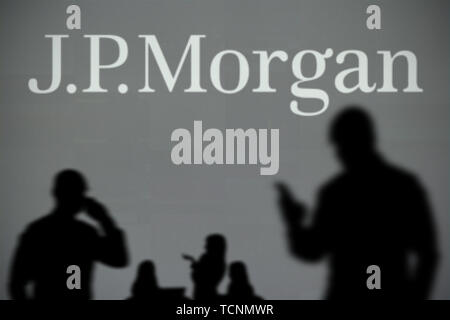 The JP Morgan logo is seen on an LED screen in the background while a silhouetted person uses a smartphone in the foreground (Editorial use only) - Stock Image