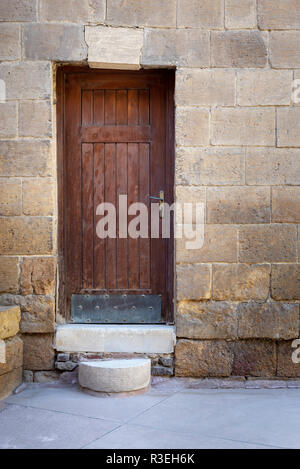 Old wooden door framed by bricks stone wall at the courtyard of al Razzaz historic house, Darb al Ahmar district, Old Cairo, Egypt - Stock Image