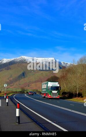 Eddie Stobart Lorry, The main A66 road to the Lake District,Cumbria England, UK - with snow capped Blencathra mountain visible in the distance. - Stock Image