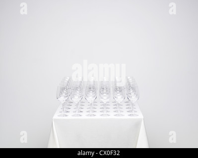 Rows of empty wine glasses on a table. Similar photo available with one glass full. - Stock Image
