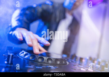 Dj mixing at party festival with blue light and smoke in background - Summer nightlife view of disco club inside. Focus on hand - Stock Image