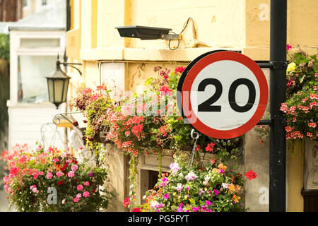 A 20mph British road sign attached to a street lamp on a city street. The sign is next to a residential property decorated with  hanging baskets - Stock Image