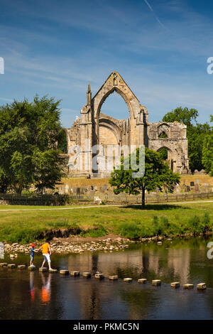 UK, Yorkshire, Wharfedale, Bolton Abbey, stepping stones over River Wharfe below Augustinian Priory ruins - Stock Image