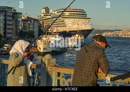 An elderly lady angles from Galata Bridge.  A large cruise ship is moored along the Karaköy seafront. - Stock Image