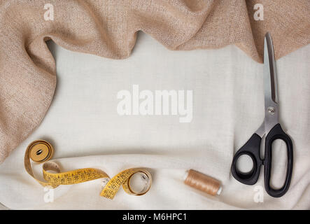 set for sewing. fabric, scissors, measuring tape, thread on light fabric. view from above - Stock Image