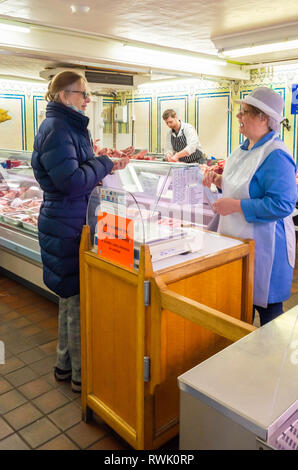 Senior lady customer in a Goodswen's traditional butchers shop in Redcar North Yorkshire chatting to the server while buying pork pies - Stock Image
