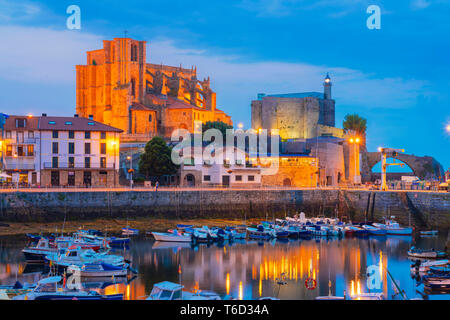 Spain, Cantabria, Castro-Urdiales, harbour, Santa Maria church and Santa Ana castle at dusk - Stock Image