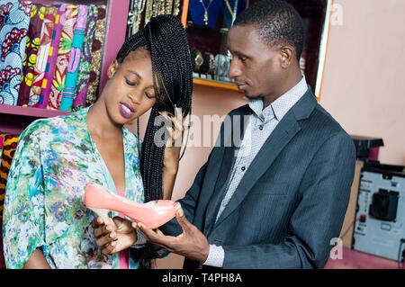 Young man proposing a shoe to his fiance in a shop and they look at her carefully. - Stock Image