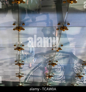 Pedestrians reflected in the glass ceiling of the entrance canopy, Metropol Hotel, Revolution Square, Moscow, Russia - Stock Image