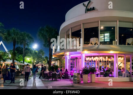 People walk along Lincoln Road Mall on Miami Beach and eat in front of Yuca; Young Urban Cuban American restaurant - Stock Image