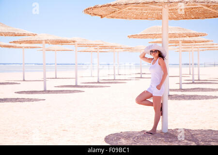 Young girl standing under an umbrella on the beach - Stock Image