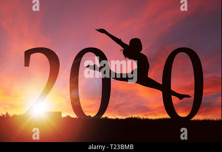 2020 New Year silhouette of a girl dancing during golden sunrise or sunset with copy space. - Stock Image