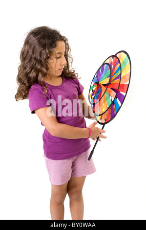 young girl holding a pinwheel isolated on white - Stock Image