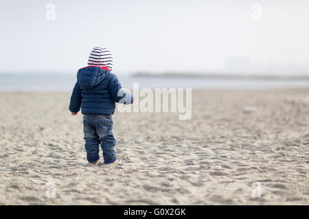 little boy standing on the beach. Eyes looking to the sea. Image from behind the boy. - Stock Image