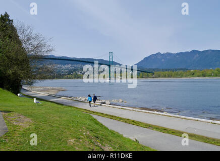 People walking on the Stanley Park seawall in Vancouver, Canada, with a view of the Lion's Gate Bridge. - Stock Image