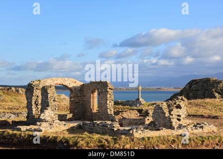 Historic 16th century ruins of St Dwynwen's church with Celtic cross on Ynys Llanddwyn Island, Isle of Anglesey, North Wales, UK - Stock Image