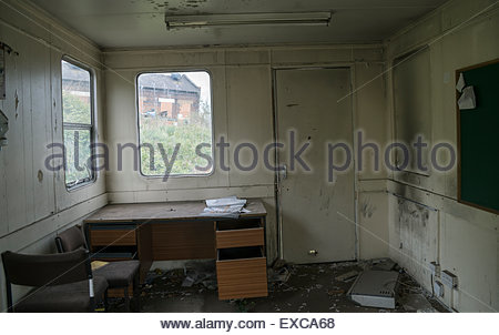 Disused and derelict portable cabin previously used as office with abandoned furniture looking out onto an industrial - Stock Image