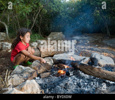 young girl in a campfire min a mediterranean forest - Stock Image