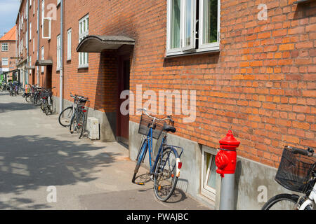 Bicycles along the apartment building wall. Copenhagen, Denmark - Stock Image