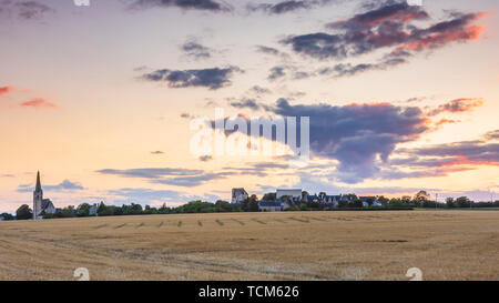 Typically french picturesque landscape with farmland and a small village at sunset - Stock Image