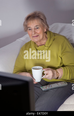 Senior lady alone watching tv holding a mug, remote control on her lap. - Stock Image