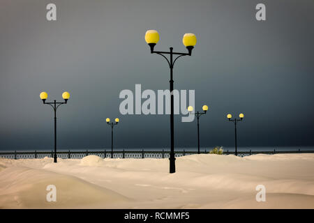 Winter park in the evening covered with snow with a row of lamps - Stock Image