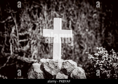 White cross on a tomb in sepia colors on a graveyard - Stock Image