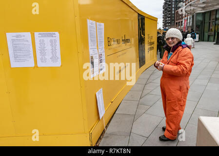 London, UK. 10th December 2018.  A protester tapes infromation on the fence at the US Embassy in the final 'Shut Guantanamo!' monthly protest of 2018 on the 70th anniversary of the Universal Declaration of Human Rights (UDHR). This declared 'No one shall be subjected to torture or to cruel, inhuman or degrading treatment or punishment' and 'No one shall be subjected to arbitrary arrest, detention or exile.' Guantanamo still has 40 detainees who have been tortured and held in indefinite detention without trial for almost 17 years. Credit: Peter Marshall/Alamy Live News - Stock Image