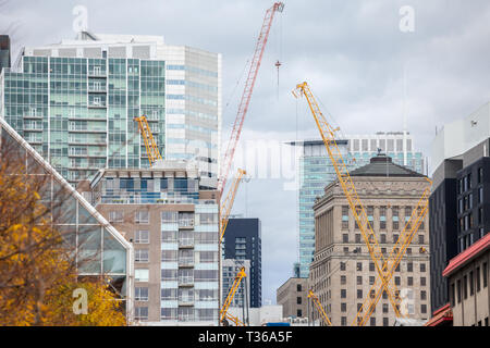 Cranes and building device on a construction site of a skyscraper in downtown Montreal, surrounded by other high rise towers and condos as well as old - Stock Image