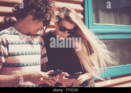 Young beautiful people couple enjoyimg and using modern cellular phone together looking the devices and enjoying the internet connection - vintage col - Stock Image