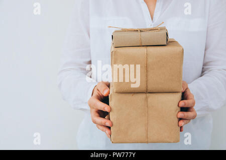 Young caucasian woman in jeans shirt holds in hands stacked gift boxes wrapped in brown craft paper tied with twine. White wall. Christmas New Years c - Stock Image