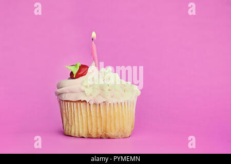 Pretty strawberry or cherry flavored frosted cupcake decorated with white chocolate shavings and one candle burning. Free space for copy text. - Stock Image