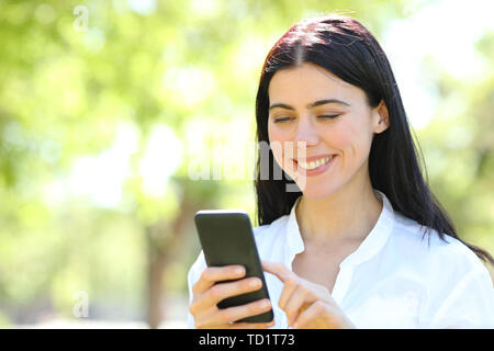 Happy beauty adult woman using smart phone standing in a park - Stock Image