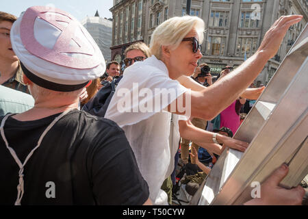 London, UK. 19th April 2019. Dame Emma Thompson climbs the ladder to speak from the large pink yacht, names after assassinated Honduran environmental activist Berta Cáceres  at Extinction Rebellion's Sea of Protest in Oxford Circus around. She came as a part of the activities to show 'Love For The Earth' on the 5th day of the occupation, but which were interrupted by police shortly after she spoke. Credit: Peter Marshall/Alamy Live News - Stock Image